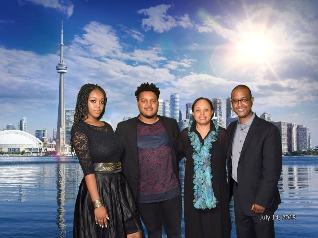 alumnus adrian peel standing with two women and one man with the toronto skyline in the background