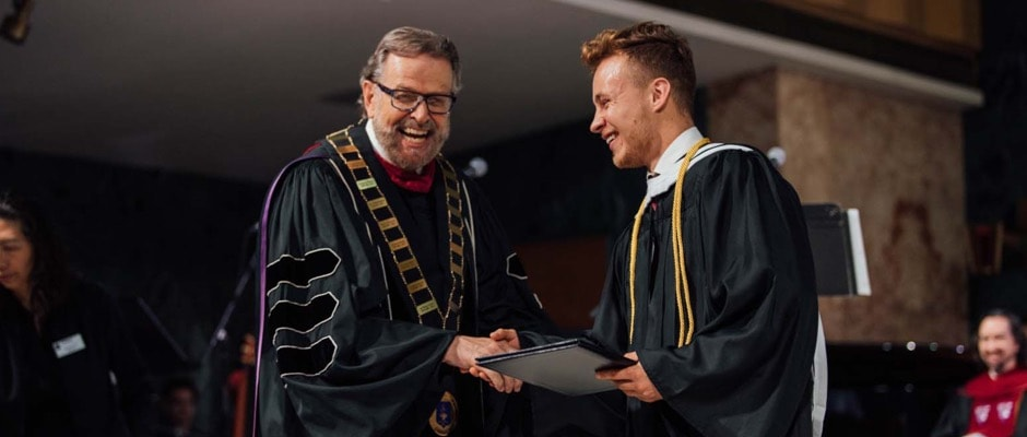 President Nelson presenting the graduation certificate to a graduate