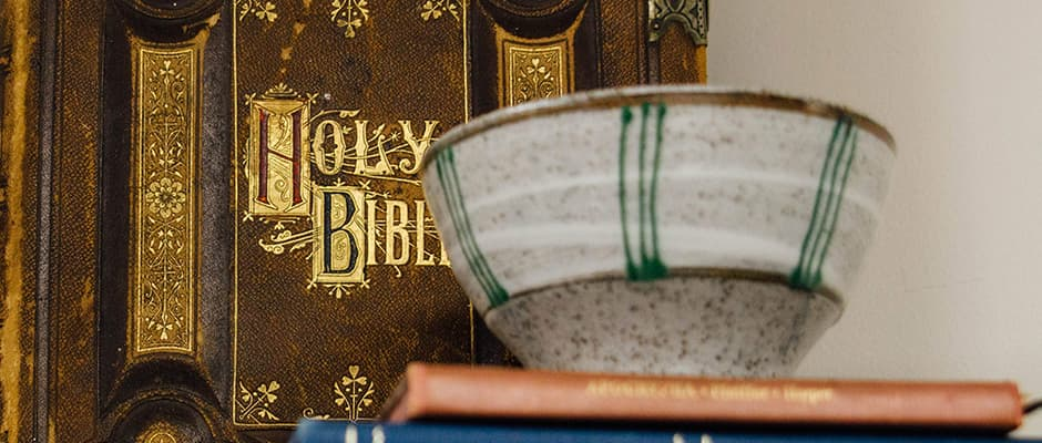 Holy Bible and a bowl on a stack of books