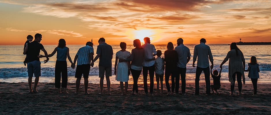Family standing on the beach at sunset