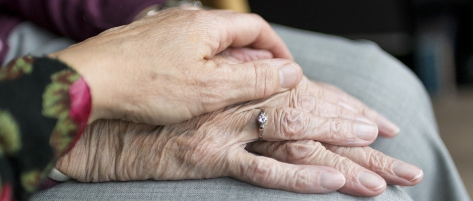 an elderly person's hand being held by a younger person's hand in sympathy