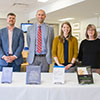 Four University College faculty pose with their recently-published books