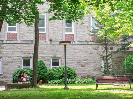 One of Tyndale courtyard with a women reading a book during the summer