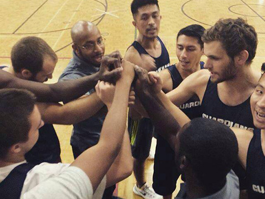 A huddle of Tyndale basketball players on the court with their hands together in the centre