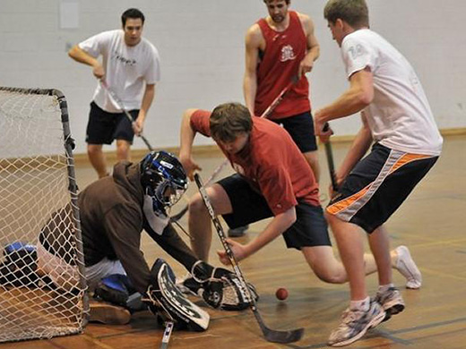 Several floor hockey players fight for control of the ball near the net as the goalie defends