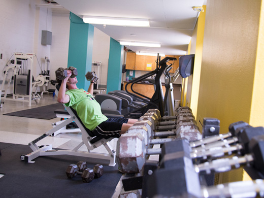 A man lifts weights in the Henderson Fitness Centre surrounded by rows of exercise equipment