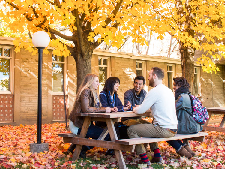 A small group of adults having a retreat in a courtyard during fall.
