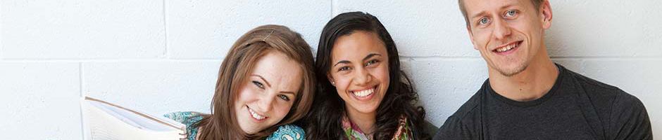 Two female students and a male student sitting against a white concrete wall smiling