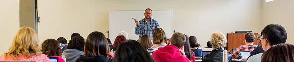 A teacher gesturing with a marker while speaking to a classroom full of students