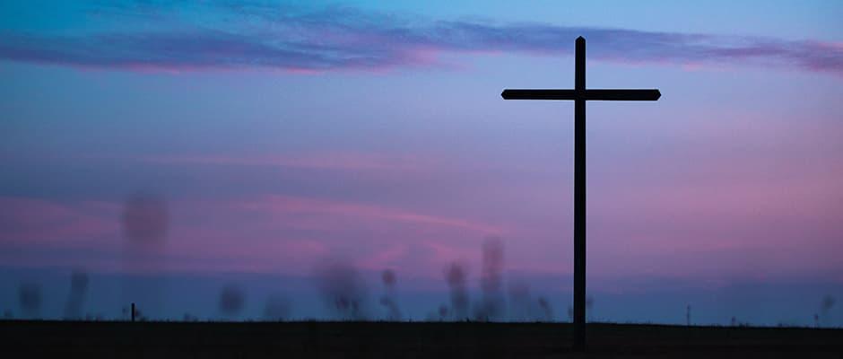 A cross in an open field at twilight