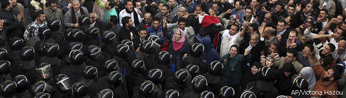 Egyptian protesters face anti-riot policemen in Cairo, Egypt, Friday, Jan. 28, 2011
