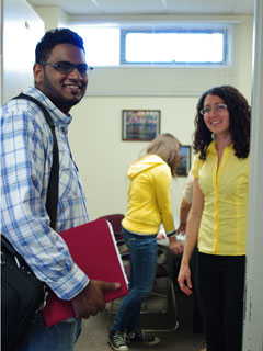 A man and a woman at the doorway to an office looking at the camera and smiling