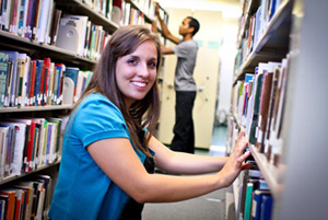 A smiling girl kneeling down between library bookshelves, with a man searching for a book in the background