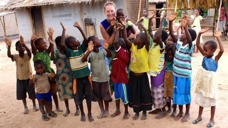 Kaitlyn Williams, a Tyndale student, in Malawi, holding up a young child and surrounded by local Malawi children