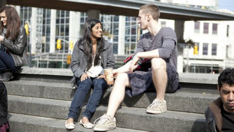 Students sitting on steps in city area