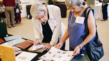 Two alumni ladies looking at yearbooks