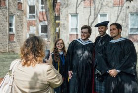 University College graduates taking picture with Dr. Benjamin Reynolds