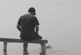 grayscale photo of man sitting on dock photo