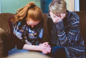 Two females praying together on a couch