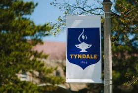 Tyndale crest on a flag hanging from a flagpole