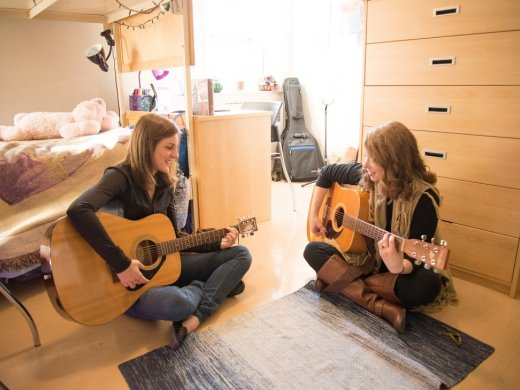Two girls in a dorm room playing guitar together