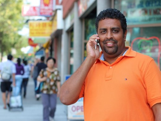 Man speaking at phone on a busy street looking at the camera