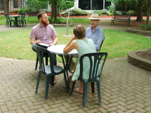Two students and a professor sitting at a table in a courtyard