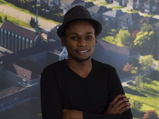 Axel Kazadi posing in front of a poster of Tyndale's Bayview Campus