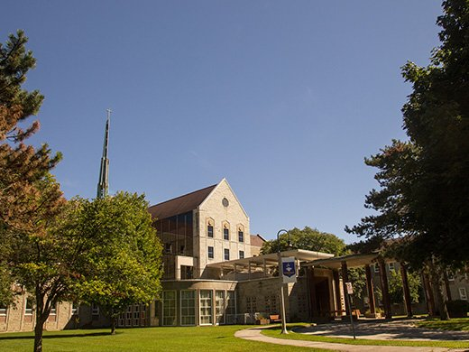A wide-angle view of Tyndale's Bayview campus front entrance on a sunny day, with surrounding trees