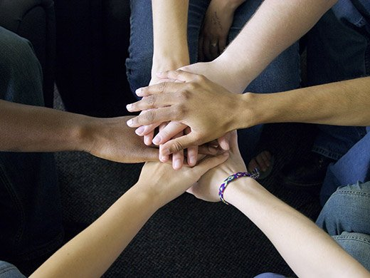 A view from above of a circle of six people's hands piled on top of one another