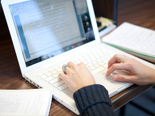 Closeup of a person's hands on a laptop keyboard, with books and notepads on the desk