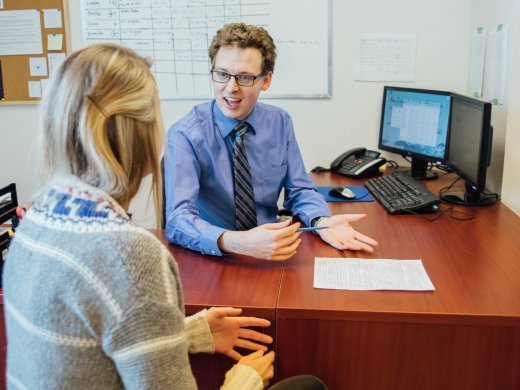 the Learning Specialist sitting at a desk explaining something to a female student about a writing assignment.