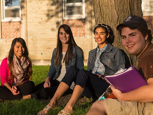 Four young students, three women and one man, sitting on the grass under a tree, looking at the camera and smiling