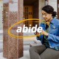 A woman on her phone and the word abide