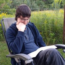 Isaac Walsh reading a book while sitting in a lawn chair in front of some tall flowers
