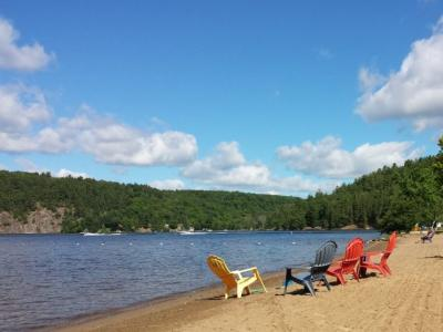 Yellow, blue, and red muskoka chairs line the sandy beach on Mary lake on a birght, sunny, summer day.