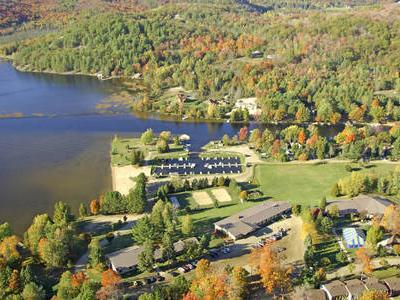 arial view of Muskoka Bible Centres multiple buildings on Mary lake and surrounding forest in fall colours of orange, red, and yellow.