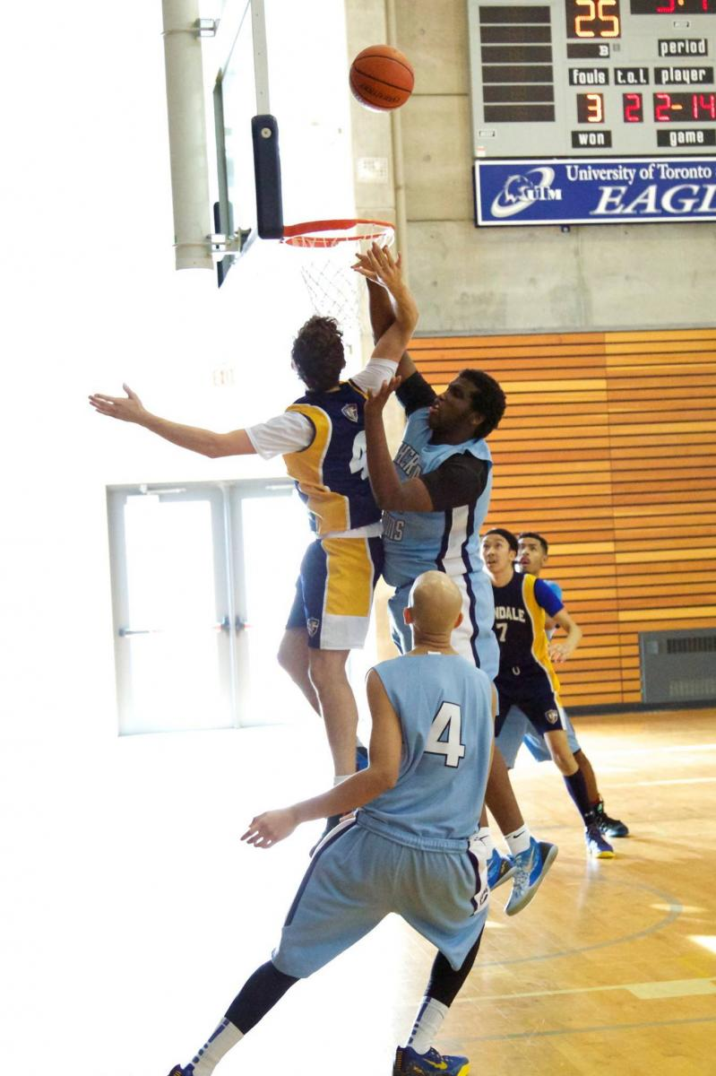 five basketball players vying for control of the ball