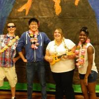 4 smiling people, two male and two female, wearing leis and posing in front of a painted backdrop