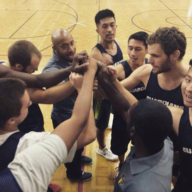 Tyndale basketball players standing in a circle team huddle