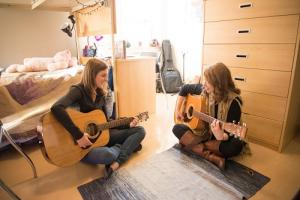 Two girls playing guitar in their dorm room