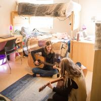 Students playing guitar in dorm room