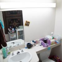 A residence bathroom with overhead view of sink, mirror, and counter covered with beauty products