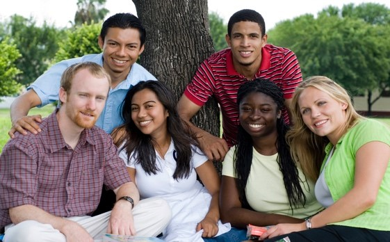 Group of smiling young people under a tree