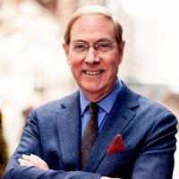 close up head shot of author Gary Chapman in glasses and a suit with his arms crossed