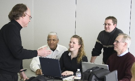 A professor teaching while four students look at him