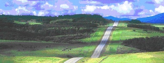 Landscape shot showing a vast expanse of hills some with trees and a road running through it