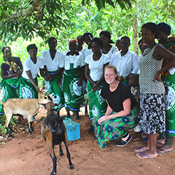 Kaitlyn Williams, a Tyndale student, in Malawi, crouching next to a couple of animals and surrounded by local Malawi residents