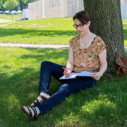 Kristen Wood sitting by a tree and writing