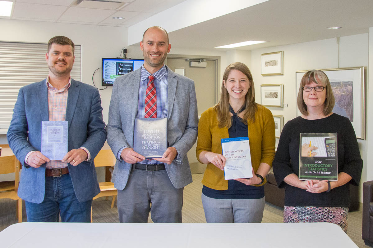 Four University College professors pose with their recently-published books